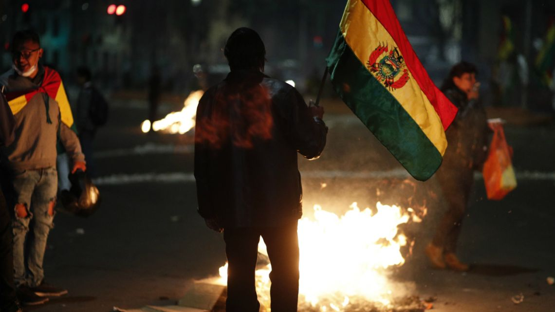 Protesters surround a burning barricade in La Paz