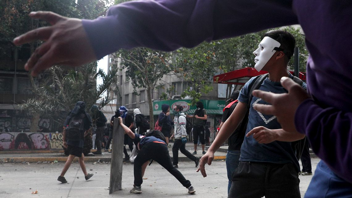 Masked demonstrators clash with the police during an anti-government protest in Santiago, Tuesday, November 5, 2019.