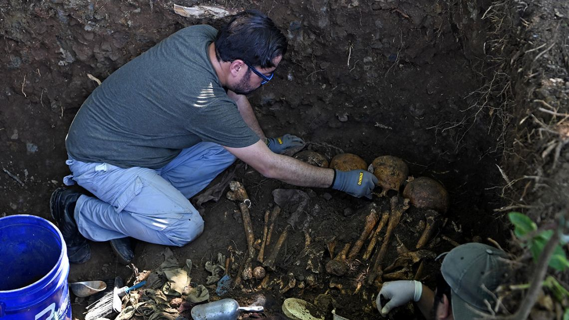 A forensic expert works on the exhumation of human remains at the Yancolo hamlet, in Cacaopera, El Salvador, on November 6, 2019.