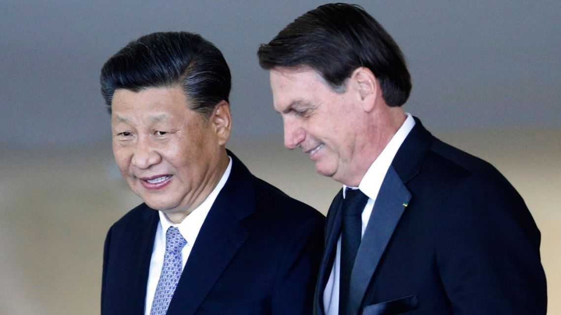 China's President Xi Jinping, left, walks with Brazil President Jair Bolsonaro, upon the Chinese leader's arrival for a bilateral meeting on the sidelines of the 11th edition of the BRICS Summit, at the Itamaraty Palace, in Brasilia, Wednesday, November 13, 2019.