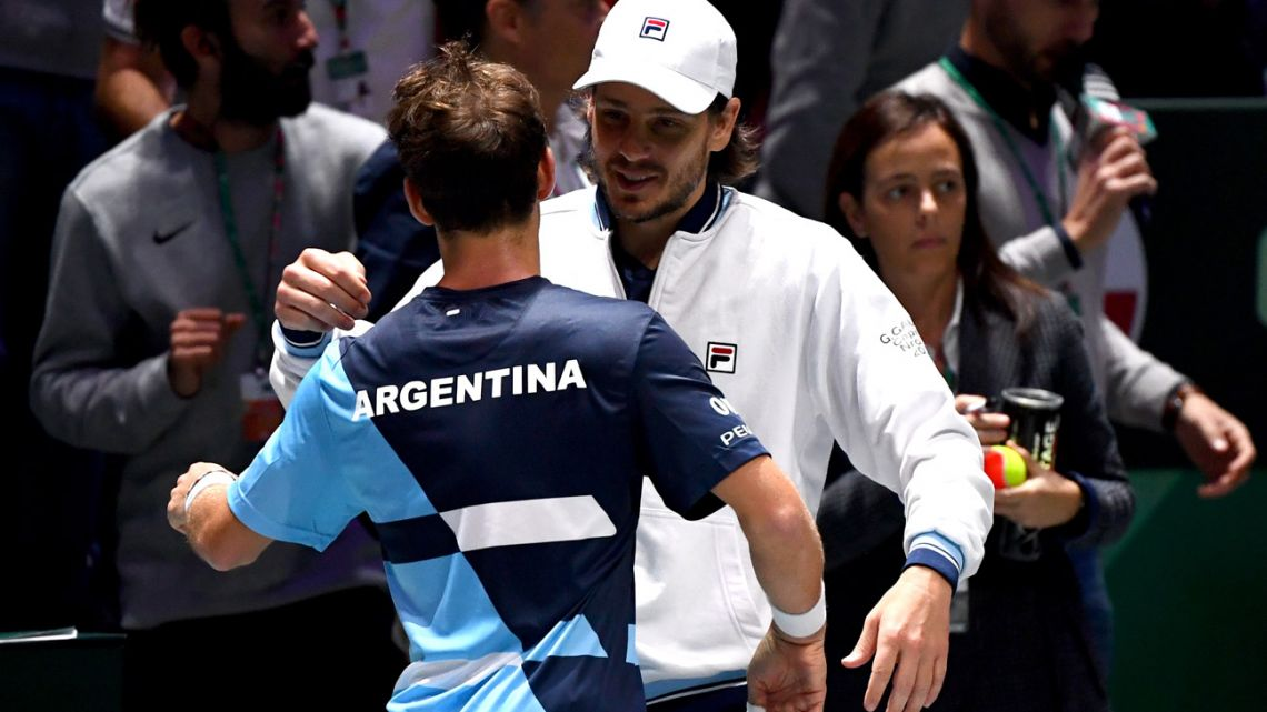 Argentina's Diego Schwartzman (left) celebrates with captain Gastón Gaudio after winning his singles tennis match against Chile's Cristian Garin at the Davis Cup Madrid Finals 2019 in Madrid on November 19, 2019.