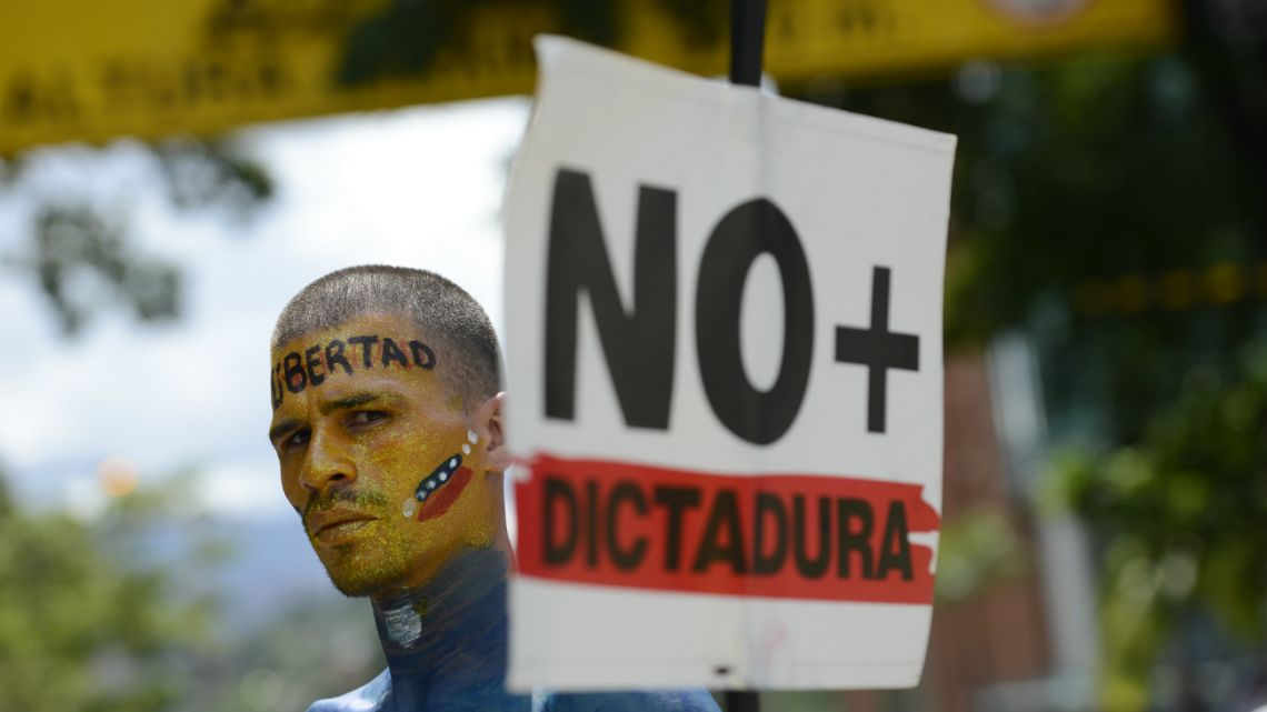 "A man holding a sign with a message that reads in Spanish: ""No more dictatorship,"" takes part in a demonstration led by opposition politician Juan Guaido, who's urging masses into the streets to force President Nicolas Maduro from power, in Caracas, Venezuela,"