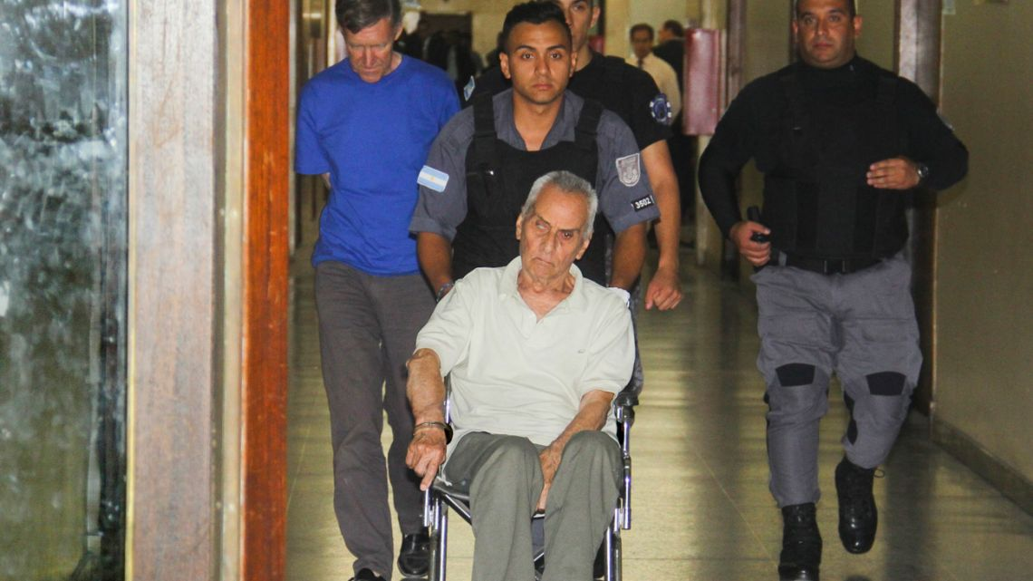 In this 2016 file photo, Reverend Horacio Corbacho, far left walking, and Reverend Nicola Corradi, handcuffed to the wheelchair, are escorted to a courtroom in Mendoza, Argentina.