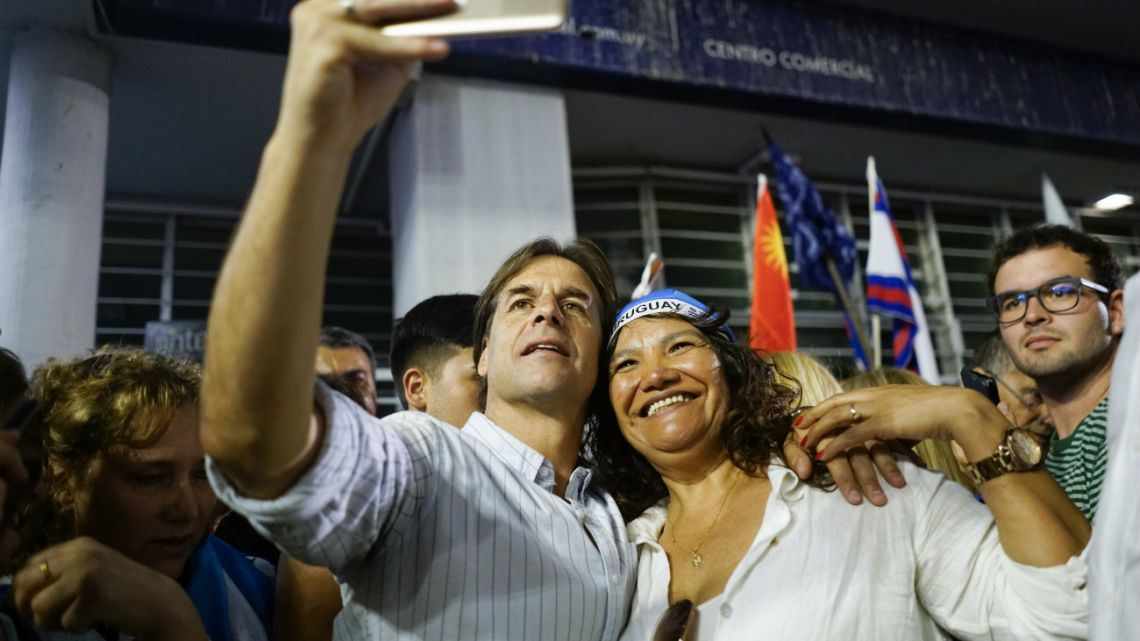 Uruguay's presidential candidate for the National Party Luis Lacalle Pou,takes a selfie with a supporter at the end of the campaign closing rally in Las Piedras, Uruguay