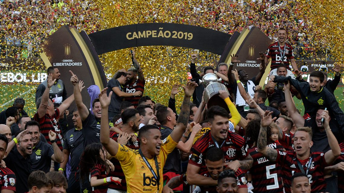 Flamengo's players celebrate on the podium with the trophy after winning the Copa Libertadores final.