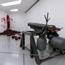 """Shooting Into the Corner II"" depicts violence as red wax bullets are shot hourly into the corner."