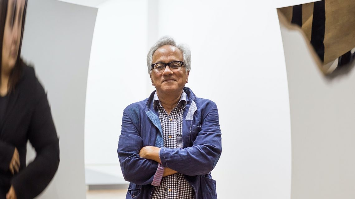 "Anish Kapoor stands in front of his piece, ""Double Vertigo."""