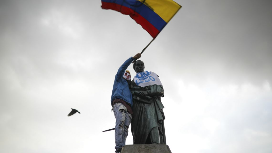 An anti-government demonstrator waves a Colombian flag after he climbed up to a statue of South American independence hero Simon Bolivar during a protest at Bolivar square in Bogota, Colombia