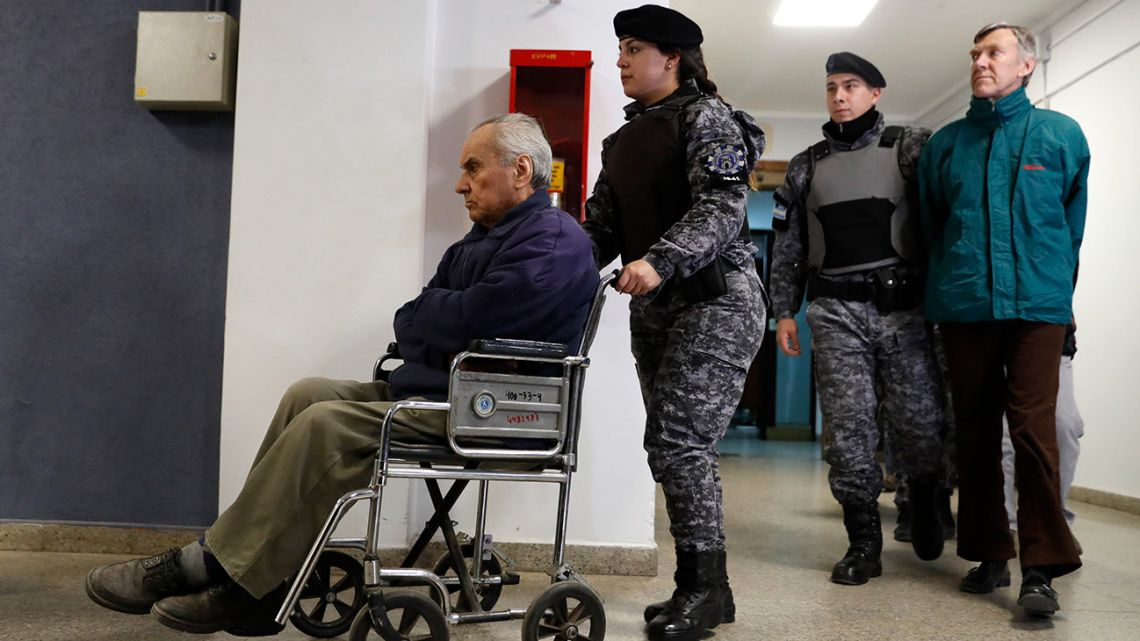 In this August 2019 file photo, Revernd Nicola Corradi, in wheelchair, and Reverend Horacio Corbacho, following behind in green, are escorted to a courtroom to attend their trial in Mendoza, Argentina.