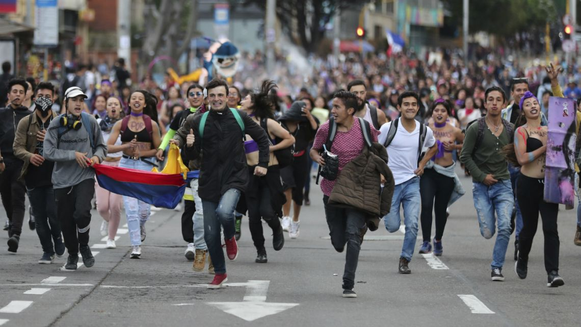Anti-government demonstrators run during a protest in Bogota, Colombia