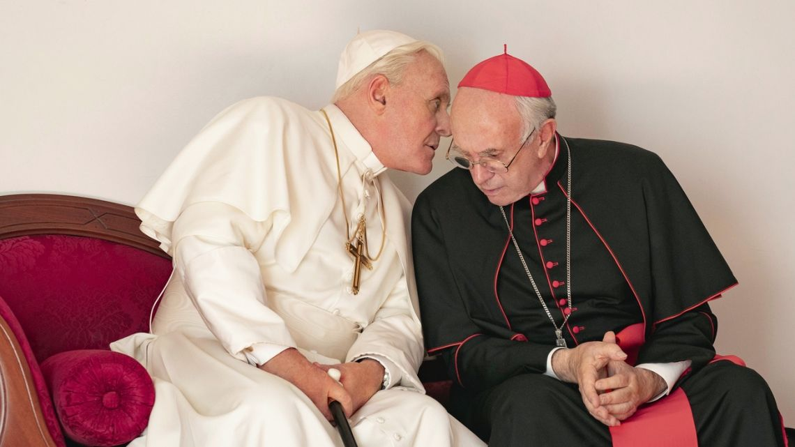 "Jonathan Pryce as cardenal Bergoglio sits to the right of Pope Benedict, played by Anthony Hopkins in a scene from ""The Two Popes."""