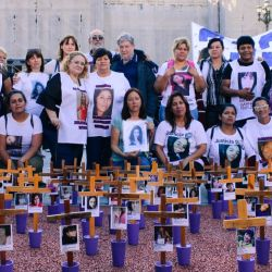 Family members of femicide victims stand behind their relatives crosses for a photo.