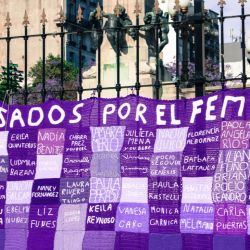 A banner of knitted names hangs from the fences of Plaza del Congreso, displaying the names of victims of femicide.
