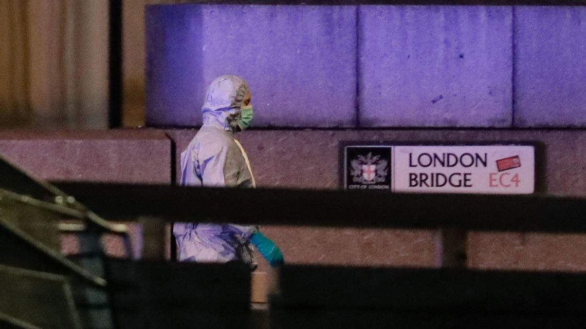 A police forensic officer walks by a sign where a man was shot dead by police on London Bridge following an incident in London, Friday, Nov. 29, 2019.