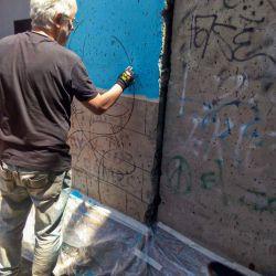 El fragmento del Muro de Berlín es intervenido por el artista y director de Arte de Editorial Perfil, Pablo Temes. | Foto:Facundo Iglesias