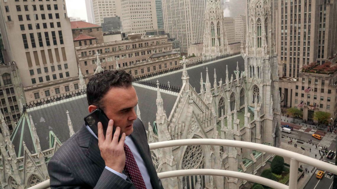Attorney Adam Slater takes a phone call on a patio outside his high-rise Manhattan office overlooking St. Patrick's Cathedral, in New York. Slater's firm is representing clients accusing the Roman Catholic Church of sexual abuse, a clientele that is rapidly growing after New York state opened its one-year window allowing sex abuse suits with no statute of limitations.