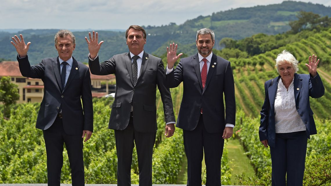 President Mauricio Macri, Brazil's President Jair Bolsonaro, Paraguay's President Mario Abdo Benítez and Uruguay's Vice-President Lucia Topolansky wave during the family photo taken at the 55th Mercosur summit in Bento Gonçalves, Rio Grande do Sul, Brazil, on December 5, 2019.