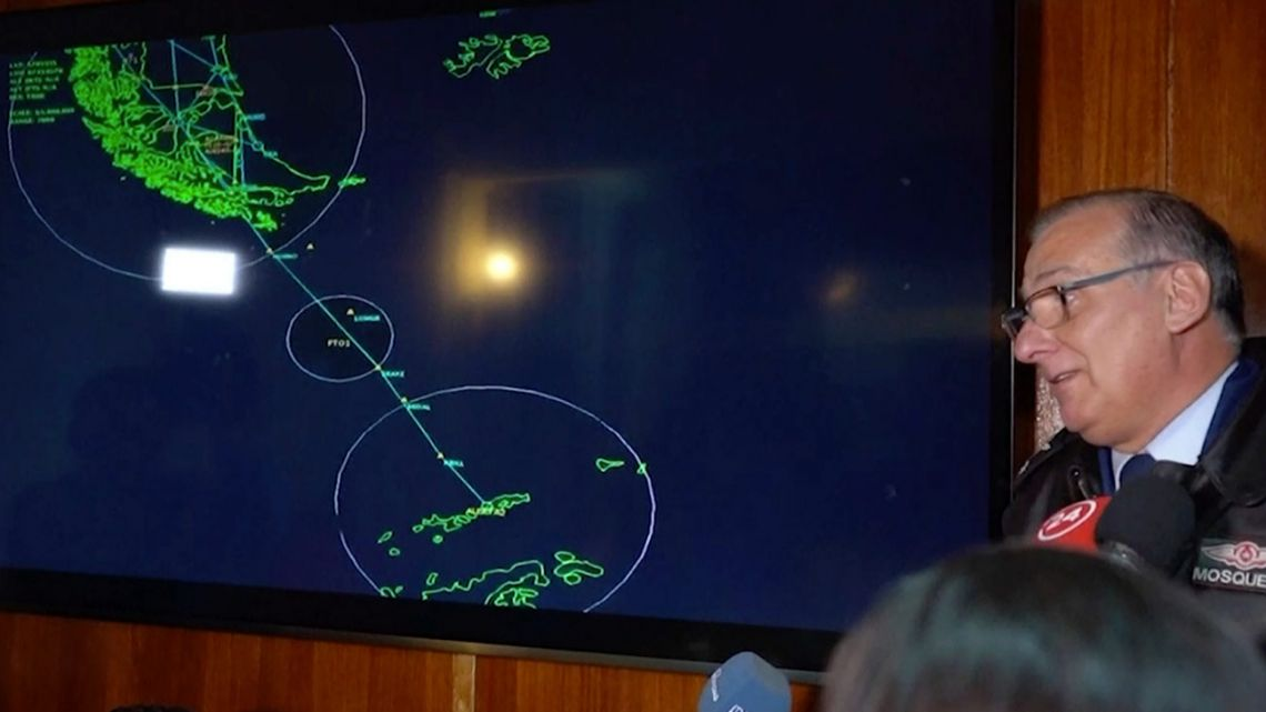 In this image made from video, General Eduardo Mosqueira, right, of the Fourth Air Brigade speaks to the media next to a map of the area where the airplane is missing, in Punta Arenas, Chile, Monday, Dec. 9, 2019. Chile's Air Force lost radio contact with a transport plane carrying 38 people on a flight Monday evening to the country's base in Antarctica, and authorities indicated several hours later that they were not optimistic about the aircraft's fate.