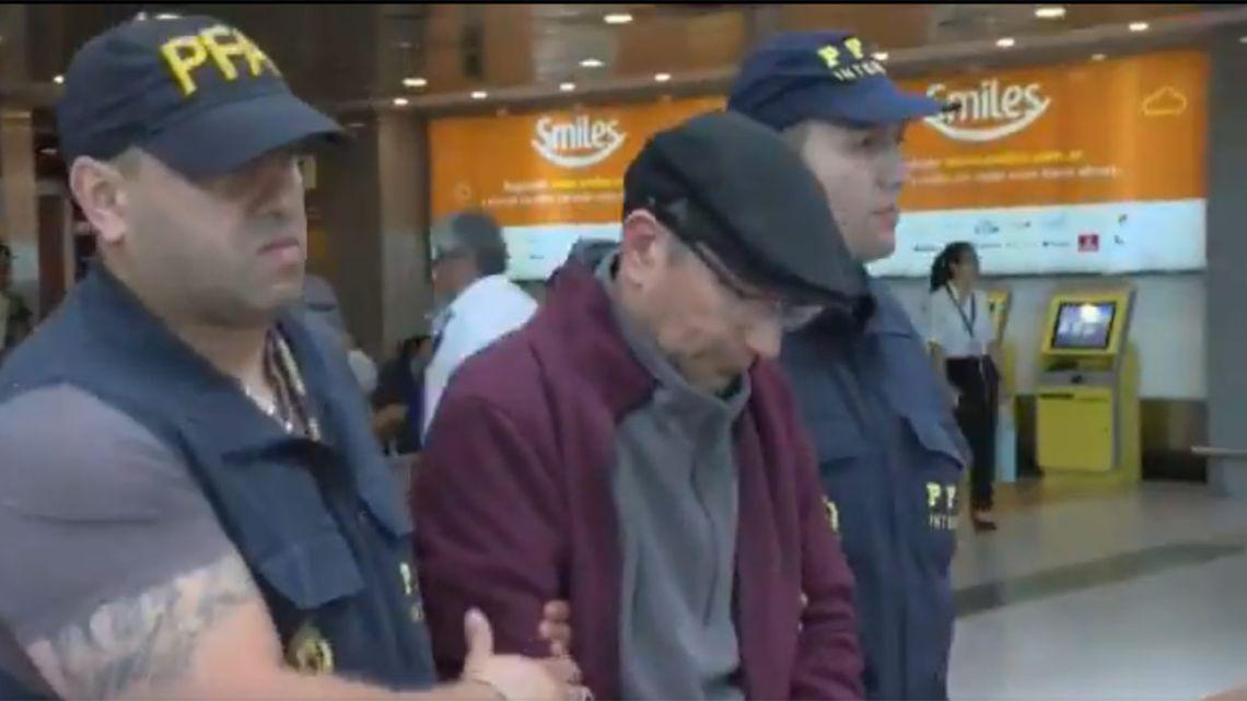 Mario Sandoval is escorted through Ezeiza international airport.