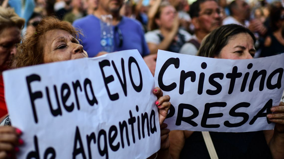 "Opponents of President Alberto Fernández protest against his government and new laws with signs reading ""Evo out of Argentina"" and ""Cristina in jail"", referring to Bolivian ex-president Evo Morales and Vice-President Cristina Fernández de Kirchner, outside Congress in Buenos Aires, on December 18, 2019."