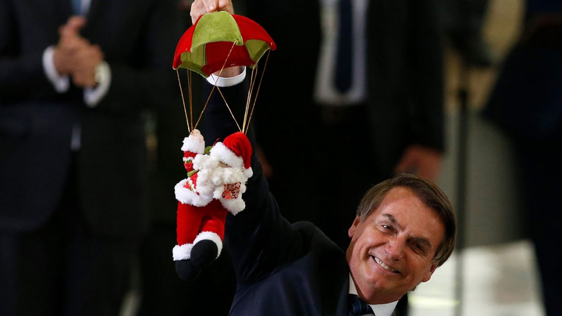 Brazil's President Jair Bolsonaro holds Santa Claus doll on a parachute, during Christmas celebrations with staff and students at the Planalto Presidential Palace, in Brasilia, Brazil, Thursday, December 19, 2019.