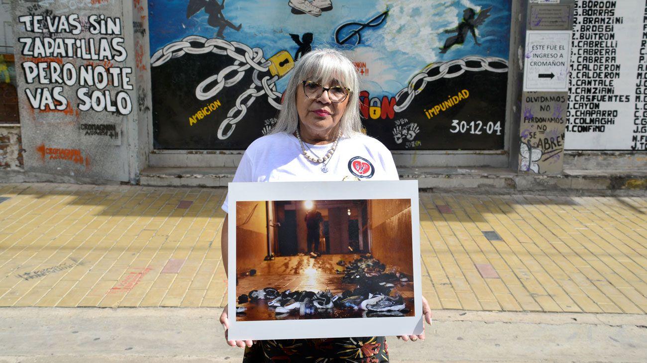MIRAR ATRÁS. Nilda Gómez sostiene la foto de las zapatillas en la salida de emergencia del boliche, que está tapiada desde este año.