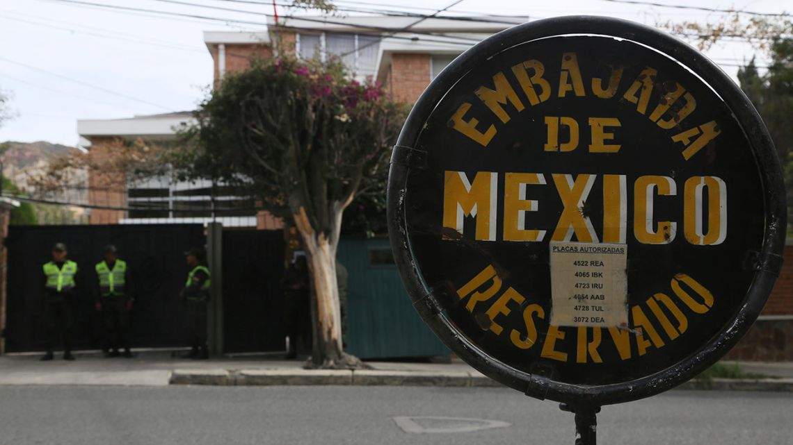 A sign announces Mexico's Embassy, where Bolivian police stand guard, in La Paz, Bolivia, Thursday, December 26, 2019.