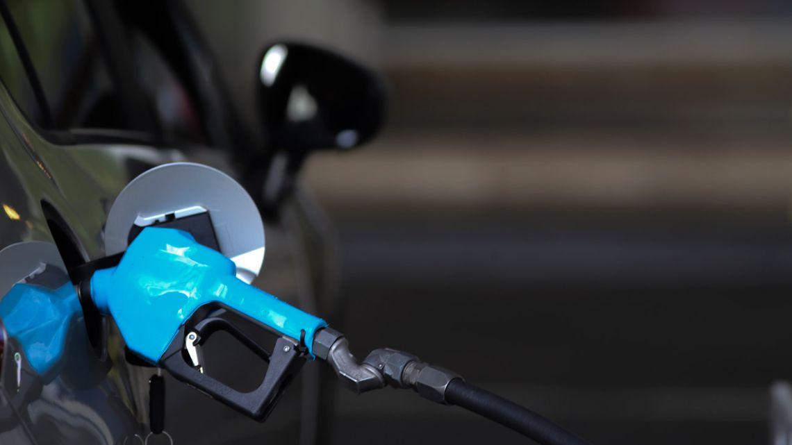 A motorist fills up his tank at a petrol station.