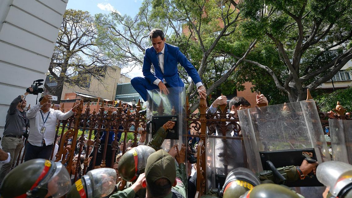 Juan Guaidó, Venezuela's opposition leader, tries to climb the fence to enter the compound of the National Assembly, after he and other opposition lawmakers were blocked by police from entering a session to elect new Assembly leadership in Caracas, Venezuela, Sunday, January 5, 2020.