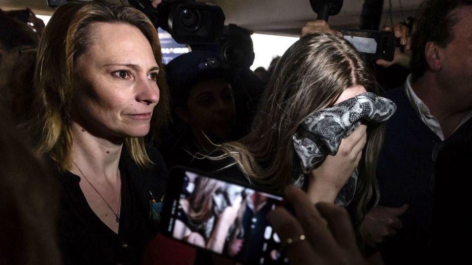 Una adolescente británica condenada por acusar falsamente a un grupo de israelíes de violación en grupo, se cubre la cara cuando llega con su madre al Tribunal de Distrito de Famagusta, en Paralimni.