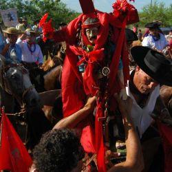 Centenares de caballos lideran la procesión con una cruz doble al frente.