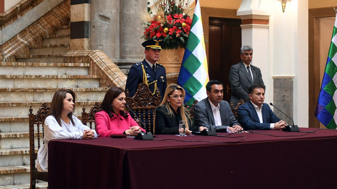 This handout picture released by Bolivian Presidency shows interim president Jeanine Añez speaking next to Bolivian Chancellor Karen Longaric (second left), Communications Minister Roxana Lizarraga (left), Minister of Government Yerko Nuñez (second right) and Defence Minister Fernando López (right) during a press conference in La Paz on December 30, 2019.