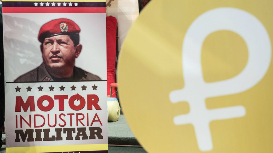A billboard featuring an image of late Venezuelan president Hugo Chavez sits next to signage for the Petro, Thursday, April 26, 2018
