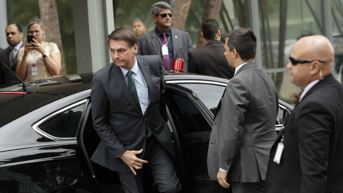 President Jair Bolsonaro exits his car for a meeting with military commanders at the Defense Ministry in Brasilia, Brazil, Tuesday, Jan. 7, 2020