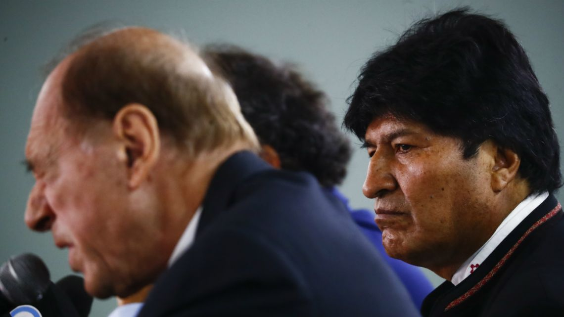 Bolivia's former President Evo Morales listens to his legal advisor Eugenio Zaffaroni during a press conference in Buenos Aires, where Morales is currently living, Thursday, Jan. 2, 2020.