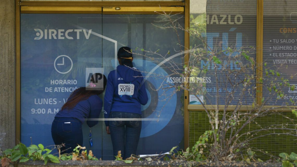 Clients wait to enter the DirecTV headquarters in Caracas, Venezuela.