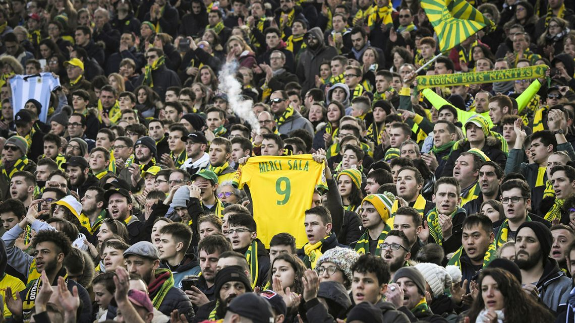 "In this photograph taken on February 10, 2019, a FC Nantes supporter holds a #9 jersey reading ""Thank you Sala"" in memory of late Argentine forward, Emiliano Sala."