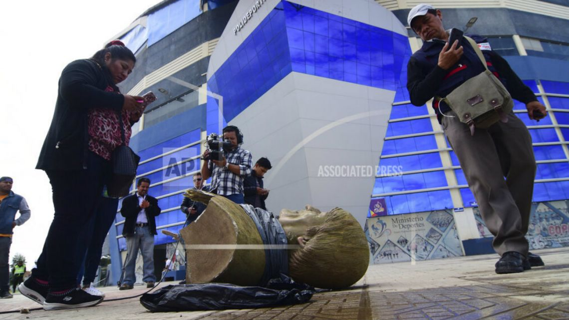 Members of the media take images of a destroyed bust of Bolivia's former President Evo Morales, after it was knocked down on the orders of Bolivia's sports minister.