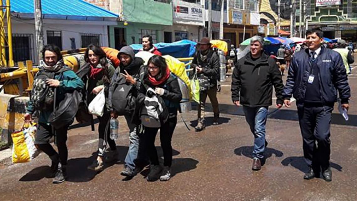 Handout photo distributed by the Peruvian Migrations Service of tourists being escorted by authorities as they walk towards the borderline with Bolivia.