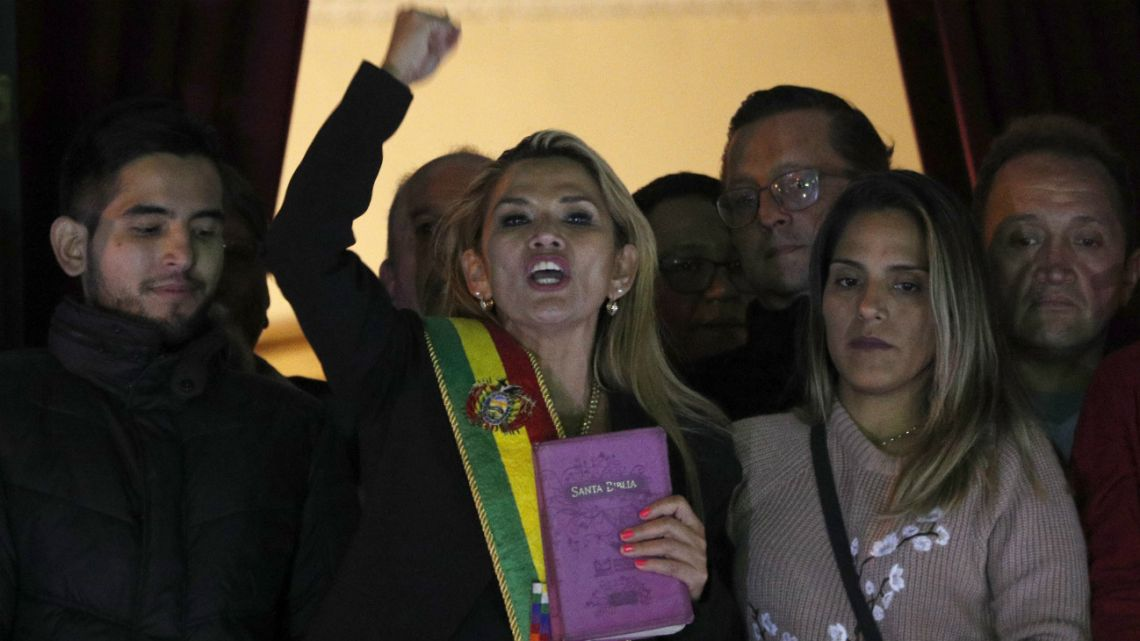 In this Nov. 12, 2019, the Senate's second vice president and opposition politician Jeanine Añez, center, wearing the presidential sash and carrying a Bible, declared herself interim president of the country, in Bolivia