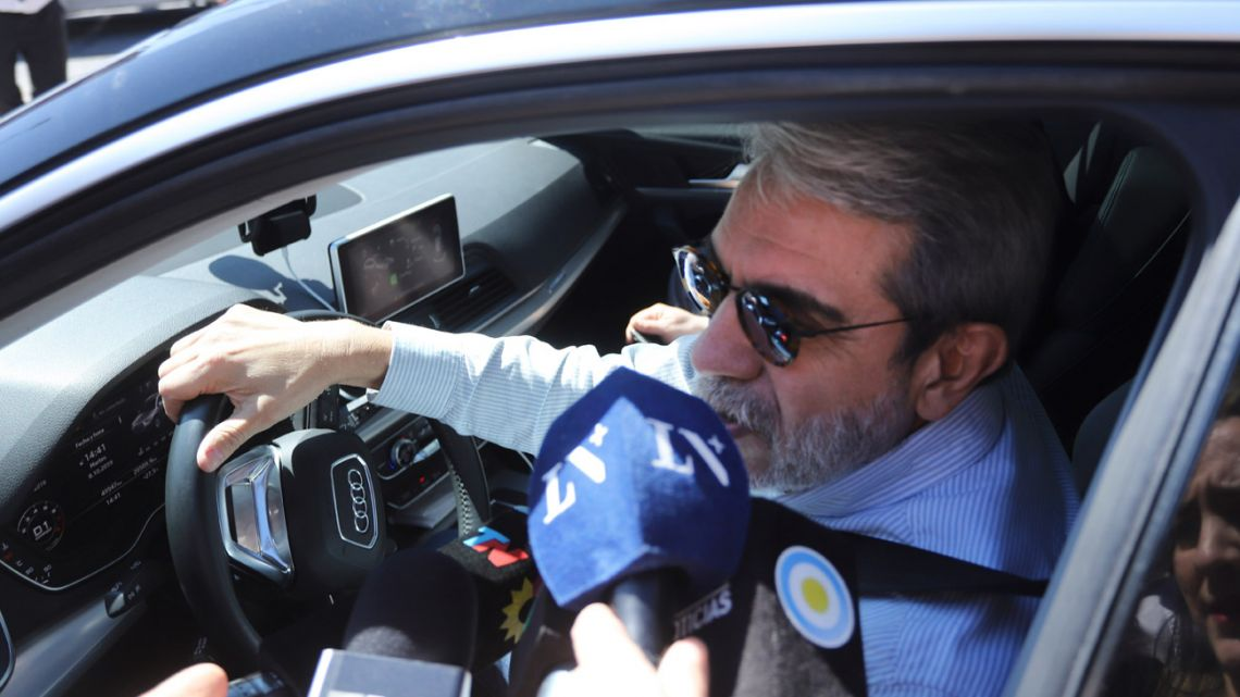 Aníbal Fernández speaks to reporters from his car in this October 2019 photo.