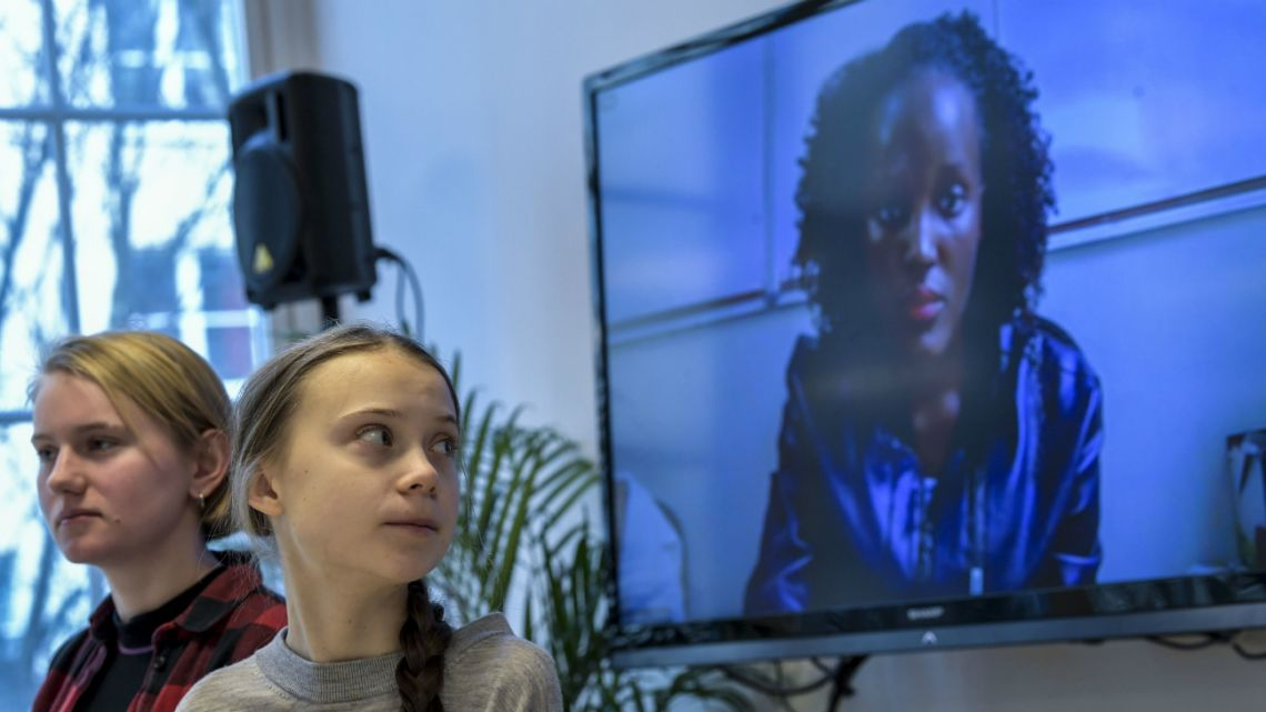 Swedish climate activists Greta Thunberg (Center) and Ell Ottosson Jarl (Left) sit in front of a screen displaying Vanessa Nakate (Right) from the Fridays For Future movement in Uganda.
