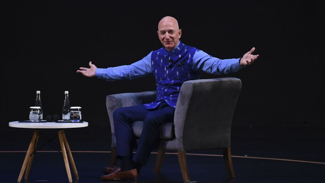 In this photo taken on January 14, 2020 CEO of Amazon Jeff Bezos (R) gestures during the Amazon's annual Smbhav event in New Delhi