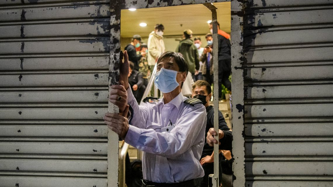 A security guard (C) wearing a facemask as a preventative measure following a coronavirus outbreak which began in the Chinese city of Wuhan, locks up a building front after stocks of face masks on February 5, 2020.
