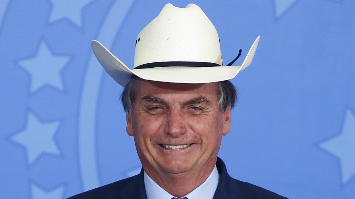 Brazil's President Jair Bolsonaro gestures wearing a hat during a ceremony with singers of country music at Planalto Palace in Brasilia, Brazil, on January 29, 2020.