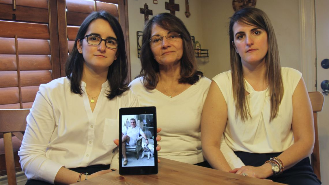 Dennysse Vadell sits between her daughters Veronica, right, and Cristina holding a digital photograph of father and husband Tomeu who is currently jailed in Venezuela with five other executives from Houston-based Citgo.
