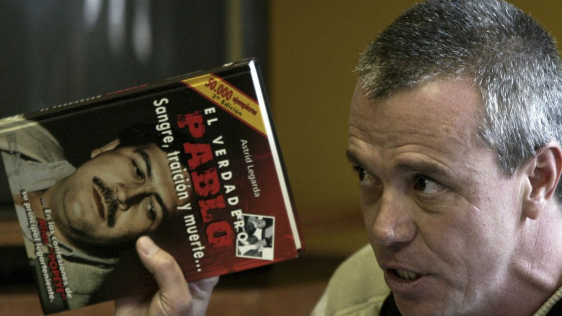 "Jhon Jairo Velasquez, a former hit man for Pablo Escobar, known by his nickname ""Popeye,"" gives testimony while holding a book titled ""The True Pablo, Blood, Treason, and Death."""