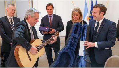 Alberto Fernández tocando la guitarra que le regaló el presidente de Francia, Emmanuel Macron.