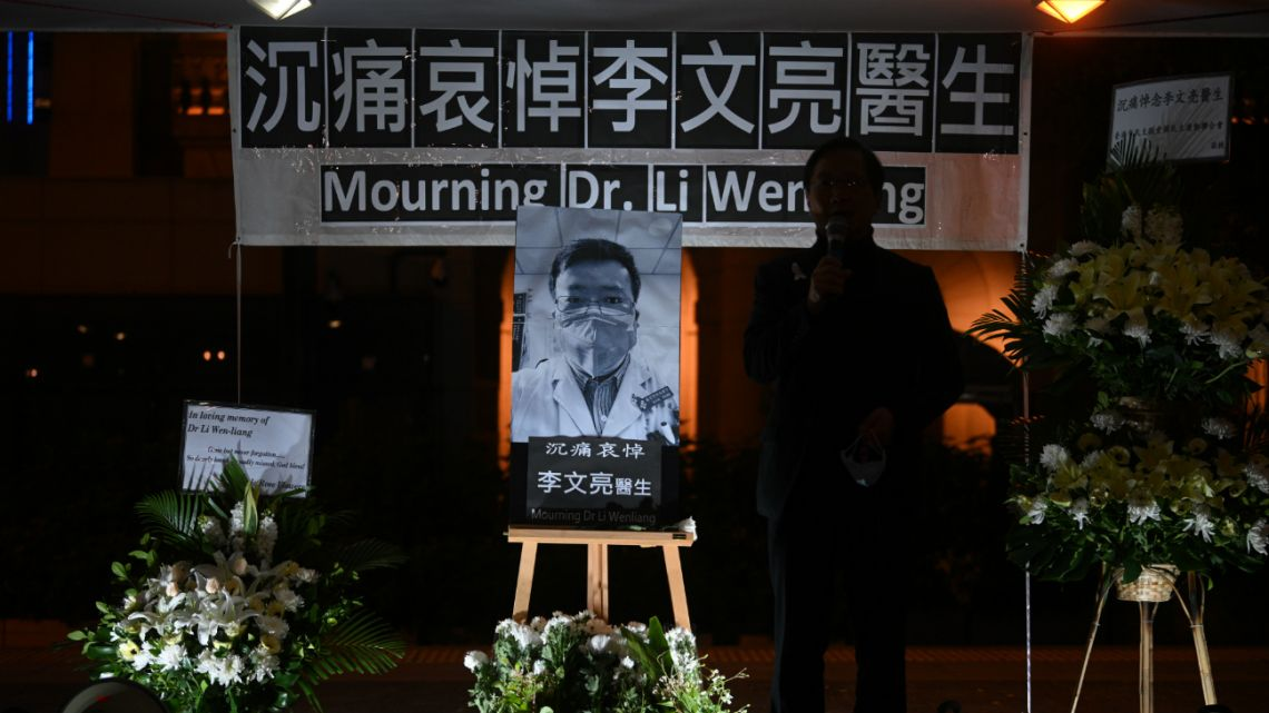 People attend a vigil in Hong Kong on February 7, 2020 for novel coronavirus whistleblowing doctor Li Wenliang (pictured C), 34, who died in Wuhan after contracting the virus while treating a patient.
