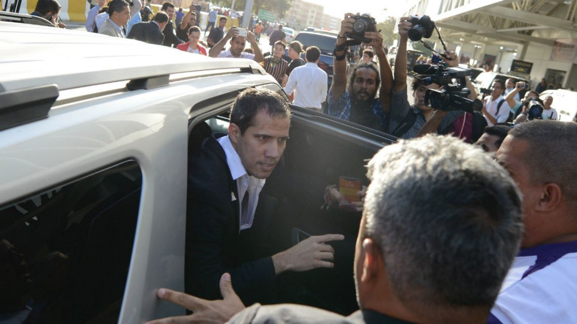 Surrounded by supporters of Venezuela's President Nicolás Maduro and members of the media, opposition leader Juan Guaido boards a vehicle after arriving at the Simon Bolivar International Airport in La Guaira, Venezuela.